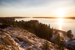 Finland, Helsinki, late autumn. Baltic sea, bay. Still water of the gulf, islands with forests. Low winter sun, dusk, pine trees on rock. Scenic peaceful Royalty Free Stock Photography