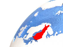 Finland on metallic globe with blue oceans. Finland in red color on globe with watery oceans and shiny metallic landmasses. 3D illustration Stock Image