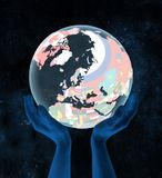 Finland on political globe in hands. Finland on translucent political globe in hands in space. 3D illustration Stock Images