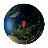 Finland in red on Earth isolated on white. Finland highlighted red on highly detailed model of planet Earth with visible city lights, plastic oceans and mountain Royalty Free Stock Photo
