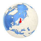 Finland in red on full globe isolated on white. Map of Finland on political globe with watery oceans and embossed continents. 3D illustration isolated on white Stock Photo