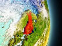 Finland in red from space. Model of Finland from Earth's orbit in space. 3D illustration with highly detailed realistic planet surface and clouds in the Stock Images