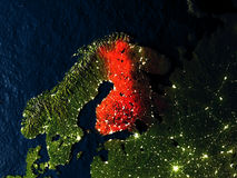 Finland in red from space at night. Finland in red at night as seen from Earth's orbit in space. 3D illustration with highly detailed realistic planet surface Stock Photos