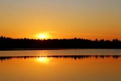 Finland: Solnedgång vid en sjö royaltyfria foton