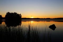 Finland: Solnedgång vid en sjö Arkivbild