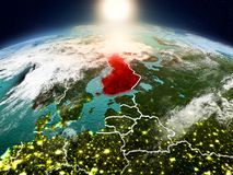 Finland in sunrise from orbit. Sunrise above Finland highlighted in red on model of planet Earth in space with visible country borders. 3D illustration. Elements Stock Photos