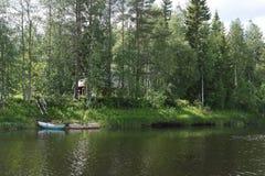 Finlandia, a casa no banco de rio Imagem de Stock