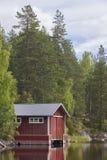 Finlandia kształtuje teren lasowego jezioro i czerwoną drewnianą kabinę Lato Zdjęcia Royalty Free