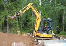 Finlandia: Uma mini máquina escavadora em um canteiro de obras imagem de stock