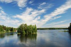 Finlandssvensk sjö med gröna öar under sommarhimmel. Arkivbilder