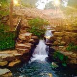 Finlay Park Waterfall in Golden Dusk. The waterfall in Finlay Park shines golden as the sunlight fades and street lamps light up the water, rocks and walkways Stock Photos