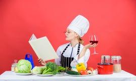 Finna receptet för varje tillfälle Damkock som söker efter laga mat recept i kokbok Nätt bok för kvinnaläsningrecept in royaltyfri bild