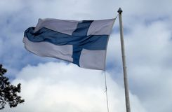 Finnische Flagge hochgezogen in einen handgemachten Fahnenmast gegen weiße Wolken Lizenzfreies Stockfoto