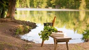 Finnische Sommerlandschafts- und -saunagegenstände auf Bank durch See Lizenzfreie Stockfotografie
