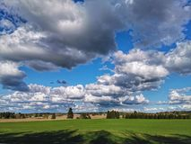 Finnish countryside landscape. Landscapes, finland, clouds, cloudy, cloudsky, beautiful, shadow, trees, nature, beautifulnature, grass, road, summer royalty free stock images