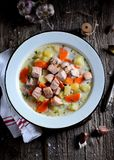 Finnish cream soup with salmon, potatoes and carrots in an old vintage plate on a wooden background. Rustic food, rustic style. Food Stock Photography