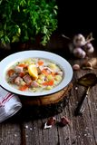 Finnish cream soup with salmon, potatoes and carrots in an old vintage plate on a wooden background. Rustic food, rustic style. Food Stock Photo