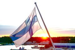 Finnish flag against the setting sun, in the evening at the port of Turku royalty free stock photography