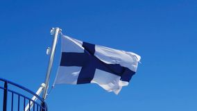 Finnish Flag before blue sky. Finnish flag blowing in wind before blue sky stock video