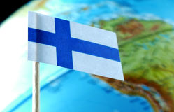 Finnish flag with a globe map as a background Stock Photography