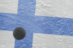 Finnish flag and the puck on the ice Stock Image