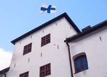 Finnish flag on the roof of the Turku castle in Finland in bright sunshine Stock Photo