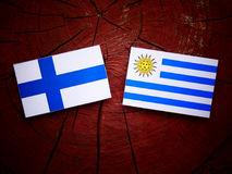 Finnish flag with Uruguaian flag on a tree stump isolated Stock Photo