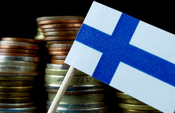 Finnish flag waving with stack of money coins Stock Image