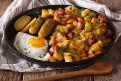 Finnish food pyttipannu: fried potatoes with sausages, eggs and. Pickled cucumbers close-up on a plate. horizontal Royalty Free Stock Photo