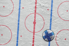 Finnish hockey puck lying on the floor Royalty Free Stock Photos