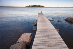 Finnish Saimaa lake landscape with wooden pier Royalty Free Stock Images