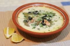 Finnish salmon soup. Traditional Finnish soup made of salmon and veggies, sprinkled with dill and served with olives and lemons Royalty Free Stock Photography