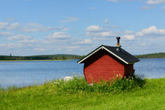 Finnish sauna on shore of blue lake Royalty Free Stock Photography