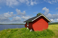 Finnish sauna on shore of blue lake Stock Photography