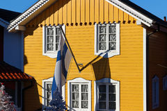 Finnish town house with flag. Yellow painted wooden house brightly in the sunlight. A traditional Finnish home with the flag of Finland and Christmas trees in Stock Images