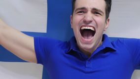 Finnish Young Man Celebrates holding the Flag of Finland in Slow Motion. High quality royalty free stock photos