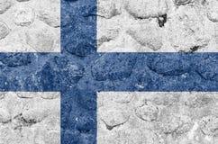 Finnland-Flagge auf einem Stein-walBelgium stock abbildung