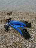 Fins and harpoon on beach. Diving equipment (fins, harpoon) on stone beach Stock Photography