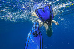 Fins snorkeler under water. Closeup of blue fins of underwater female apnea while swimming. Bubbles of water. View from behind snorkeler woman in underwater Stock Photos