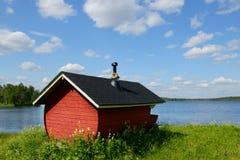 Finse sauna op kust van blauw meer Stock Afbeeldingen