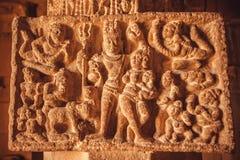 Fint exempel av indiska konstcarvings med Shiva Lord och liv av forntida folk på kolonnen av 7th århundradetempel, Indien Arkivbild