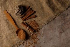 Fint - huggen av kanel i en träsked och kanelbruna pinnar på en texturerad bakgrund med textiler Top beskådar royaltyfri foto