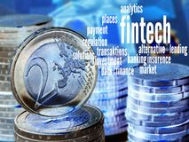 Fintech. Word cloud to FinTech (financial technology), Background: columns of coins with a visible two-Euro coin, golden Stock Image