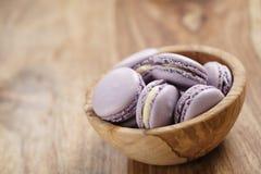 Fiołkowi macarons w drewnianym pucharze na drewnianym stołowym kąta widoku Obrazy Stock