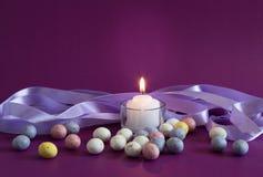 Fiołkowy Wielkanocnego jajka tło z zaświecającą świeczką i mały cętkowanym Fotografia Stock