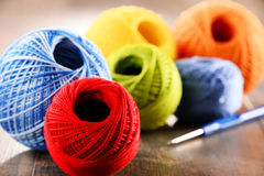 Fio colorido para fazer crochê e gancho na tabela de madeira Imagem de Stock