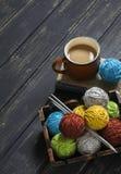 Fio de lãs e agulhas de confecção de malhas em uma bandeja do vintage, em um livro e em uma xícara de café Fotos de Stock Royalty Free