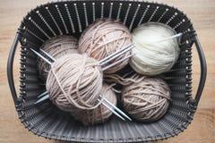 Fio do bege, e o branco, agulhas de confecção de malhas na cesta cinzenta Imagens de Stock Royalty Free