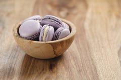 Fiołkowi macarons w drewnianym pucharze na drewnianym stole Fotografia Stock