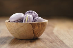 Fiołkowi macarons w drewnianym pucharze na drewnianym stole Obrazy Stock